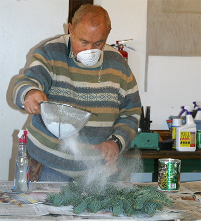 Using a seive, sprinkle the flocking lightly over the evergreen boughs. It will stick to the moistened needles.