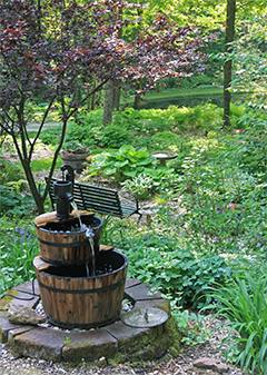 A small fountain adds the sound of trickling water to the gardens around the house.