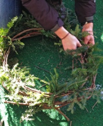 Diantha tucks hemlock clippings into the grapevine wreath