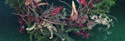 natural wreath made of grapevine, fresh greens, berries, and dried flowers