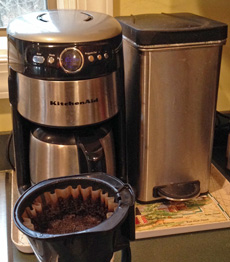 "Our compost ""bucket"" for coffee grounds and vegetable scraps sits beside the coffee pot."